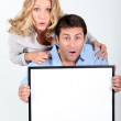 Surprised couple holding blank message board — Stock Photo #14698127
