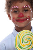 Little boy made-up in clown with lollipop — Stock Photo