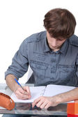 Male student at a desk — Stock Photo