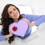Woman holding a heart-shaped box — Stock Photo