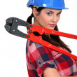 Female construction worker holding a pair of heavy-duty clippers — Stock Photo