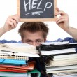 Foto Stock: Student swamped under paperwork