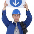 Stock Photo: Electriciholding one way sign