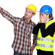 Foto Stock: Construction couple discussing problem