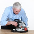 Man figuring out how to operate his new mitre saw — Stock Photo #14704767