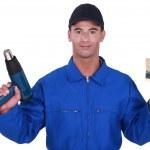 Tradesman holding a paintbrush and a screw gun — Stock Photo