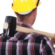 Worker resting large hammer over shoulder — Stock Photo