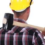 Worker resting large hammer over shoulder — Stock Photo