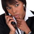 Serious businesswoman with a phone - Stockfoto