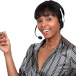 Stock Photo: Womwearing telephone headset and holding pen
