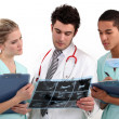 Stock Photo: A doctor and his assistants checking a radiography.