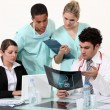 Young physician surrounded by male and female nurse — Stock Photo #14706871