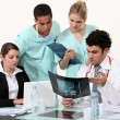 Young physician surrounded by male and female nurse — Stock Photo