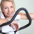 Woman resting for a moment on an exercise machine — Stock Photo #14706925