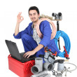 Plumber kneeling with computer doing OK sign — Stock Photo