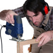 Stock Photo: Male carpenter using jigsaw.