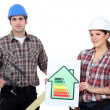 Stock Photo: Construction workers holding energy efficiency rating chart and clamp