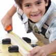 Young boy measuring a piece of wood to cut - Foto de Stock