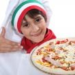 Young boy dressed as a pizza chef - Stock Photo