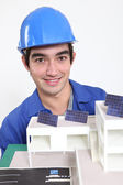 Tradesman posing with an eco-friendly building model — Stock Photo