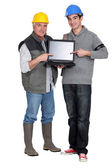 Builder and young helper pointing at laptop — Stock Photo