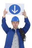 Electrician holding a one way sign — Stock Photo