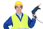 Construction worker holding a power tool — Stockfoto
