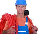 Plumber holding plunger and length of flexible pipe — Stock Photo