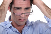 Man with glasses lowered on his nose looking annoyed — Stock Photo