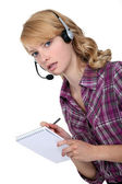 A businesswoman with a headset on taking notes. — Stock Photo