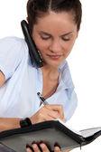 Sekreterare talar på telefonen och ta anteckningar — Stockfoto