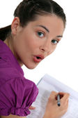 Woman writing on a clipboard — Stock Photo