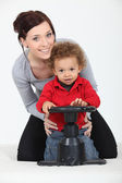 Woman and child playing with a toy steering wheel — Stock Photo