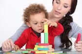 Mujer y niño jugando con bloques de construcción — Foto de Stock