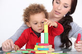 Woman and child playing with building blocks — Photo