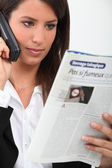 Young woman on telephone reading French magazine — Stock Photo