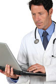 Doctor in a white coat and stethoscope with a laptop computer — Stock Photo