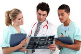A doctor and his assistants checking a radiography. — Stock Photo