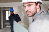 Trabalhadores transportando materiais de construção — Fotografia Stock