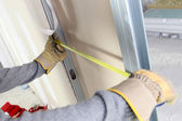 Skilled worker measuring wall — Stockfoto