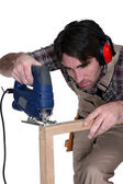 A male carpenter using a jigsaw. — Stock Photo