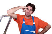 Tradesman leaning against a stepladder — Stock Photo