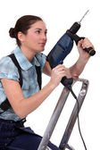 Woman holding drill whilst climbing ladder — Foto Stock