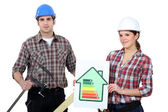 Construction workers holding an energy efficiency rating chart and a clamp — Stock Photo