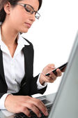 Businesswoman, with mobile telephone and laptop computer — Stock Photo