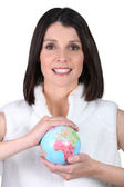 Woman holding a mini-globe — Stock Photo