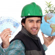 Laborer holding a globe, a green plant and twenty Euros bills - Foto Stock