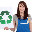 Stock Photo: Female manual worker holding recycle sign.