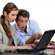 Shocked couple pointing at a laptop — Stock Photo #14711319