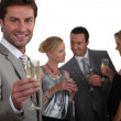 Man making a toast with champagne as his friends chat in the background - Stock Photo